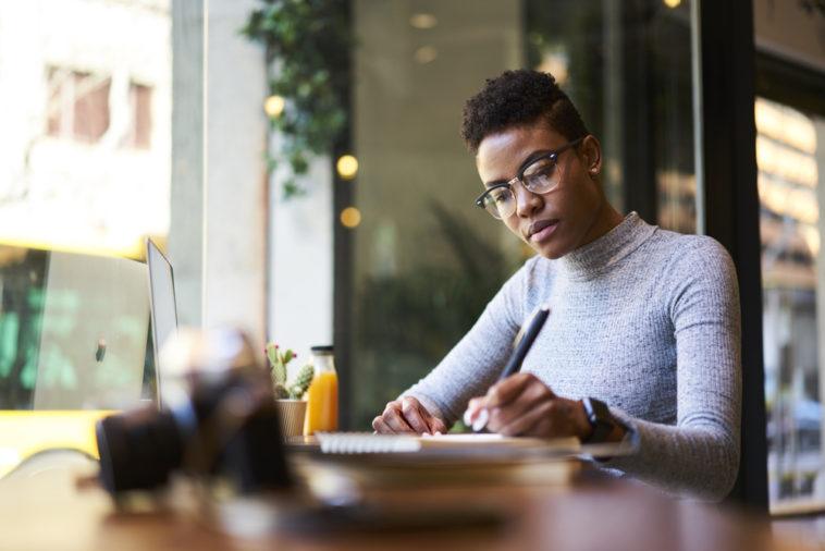 black woman journaling at desk healing trauma religious trauma spiritual wounds spirituality