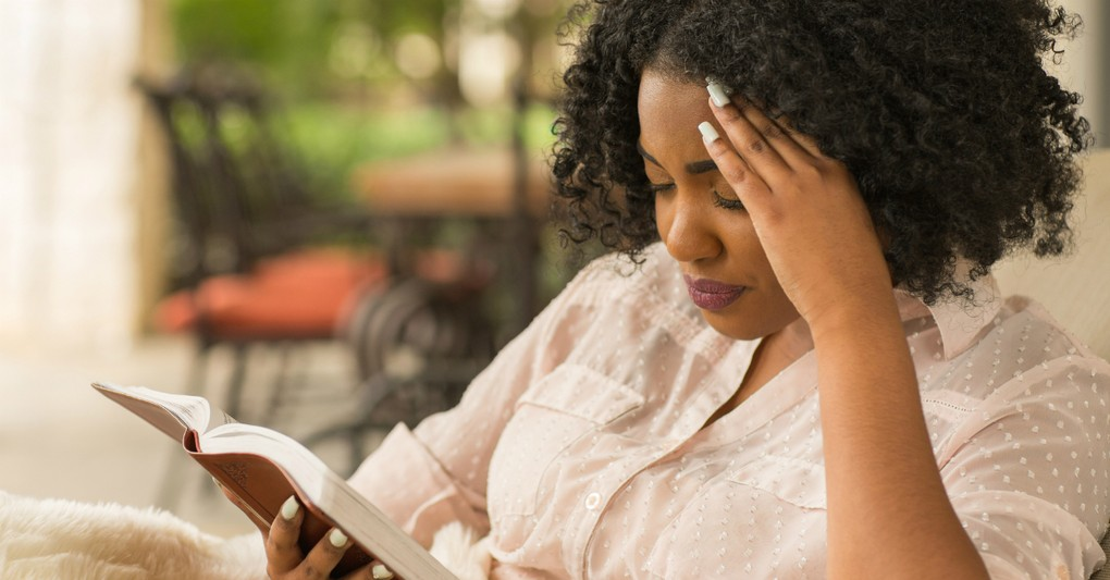 woman-reading-bible-intently-deep-in-though